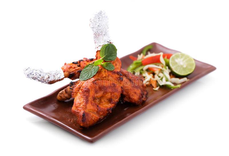 Delicious, indian tandoori chicken served with salad. Isolated on white background stock photography