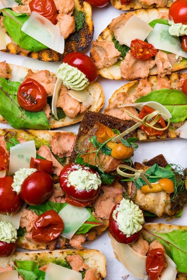 Delicious Italian antipasti bruschetta with tomato, meat pate, olives and tuna cream, mozzarella . Set of tasty appetizer. Sandwiches. close up stock image