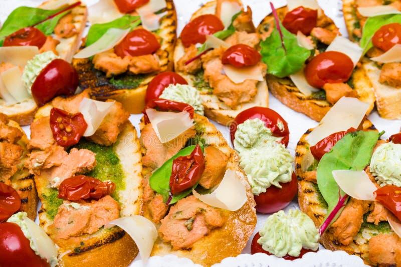 Delicious Italian antipasti bruschetta with tomato, meat pate, olives and tuna cream, mozzarella . Set of tasty appetizer. Sandwiches. close up stock photography