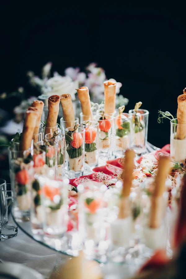 Delicious italian food table at wedding reception. Tomatoes, basil,cheese,prosciutto, greenery and bread appetizers on table at stock image