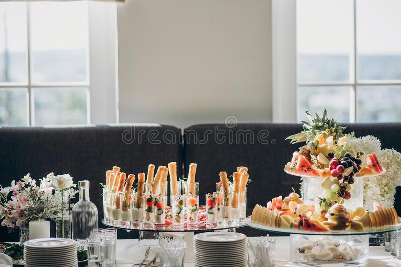 Delicious italian food table at wedding reception. Tomatoes, basil,cheese,prosciutto, greenery, bread, and fruits appetizers on stock photos