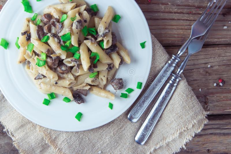 Delicious Italian penne pasta with fried creamy mushrooms champignon , onion, seasoned chopped scallions. Top view , close up. stock image