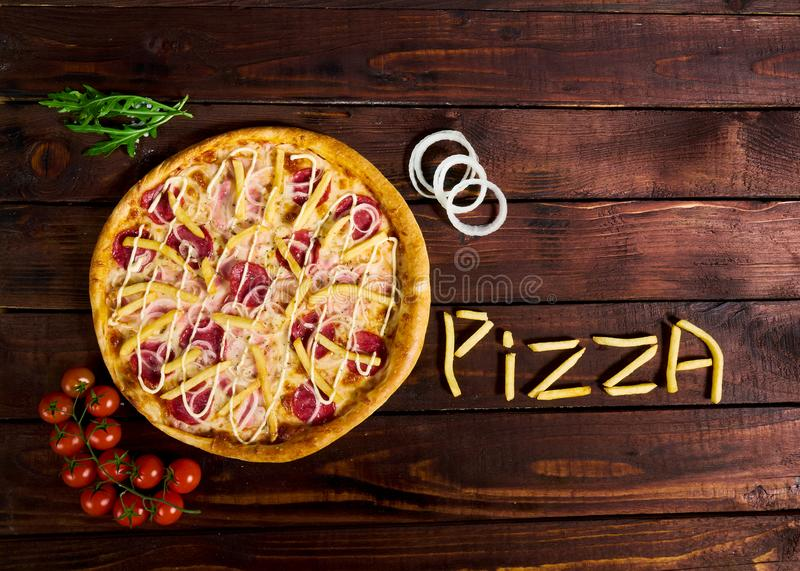 Delicious Italian pizza with French fries on a wooden table stock photography