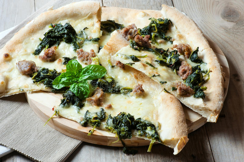 Delicious italian pizza with mozzarella, sausage and basil royalty free stock image
