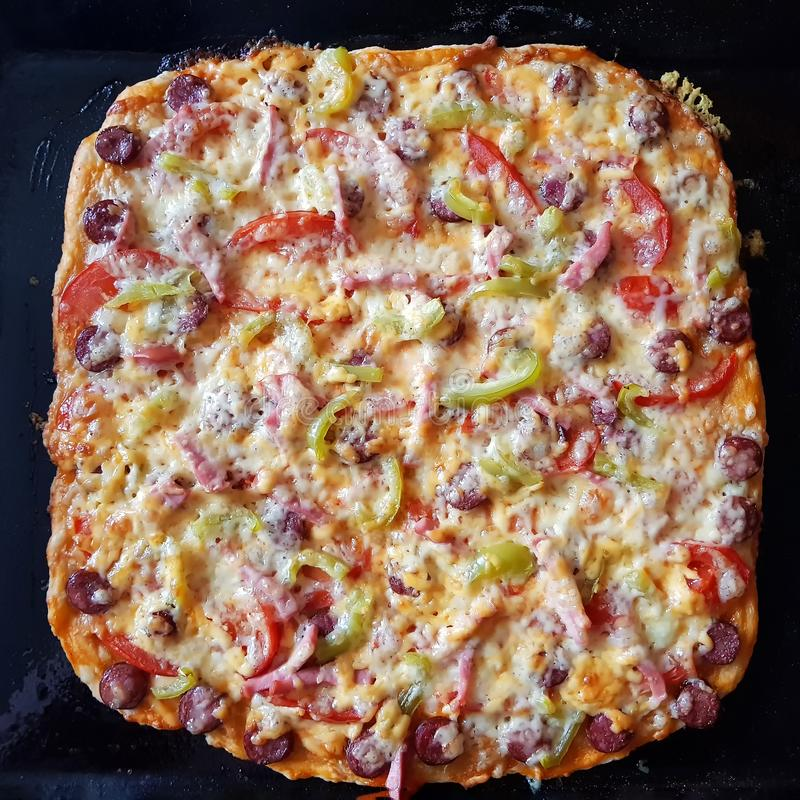 Delicious Italian pizza with pepper, tomatoes, bacon and cheese. royalty free stock image