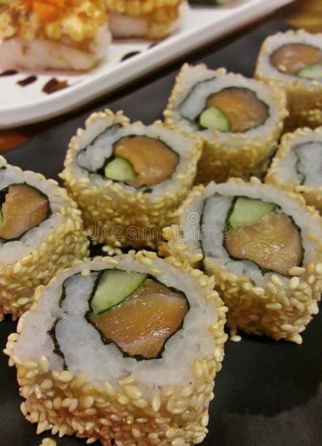 Delicious Japanese food Sushi Roll Maki of Red Salmon and Green avocado with sesame on the black plate royalty free stock image