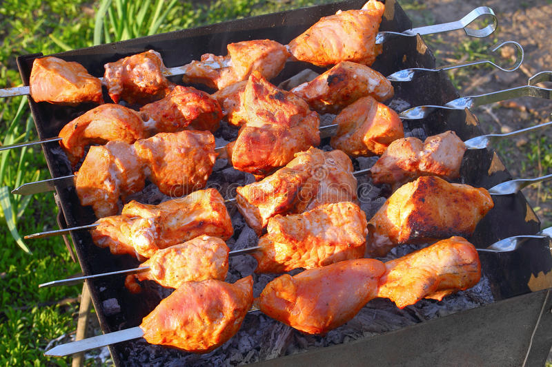 Delicious juicy chargrilled shashlik, top view. Delicious juicy chargrilled shashlik or marinated meat on metal skewers on barbecue grill in garden, view from stock photo