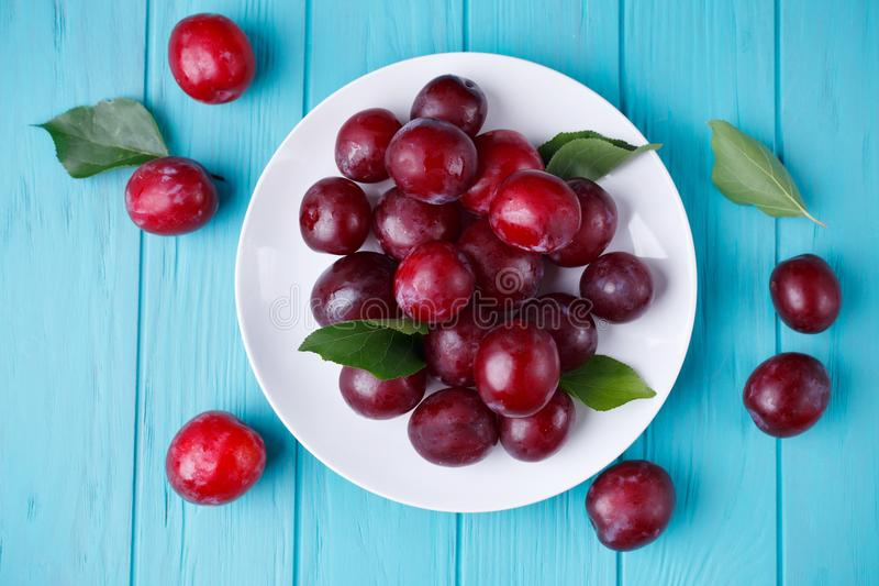 Delicious juicy fresh plums on plate on blue background, healthy royalty free stock images