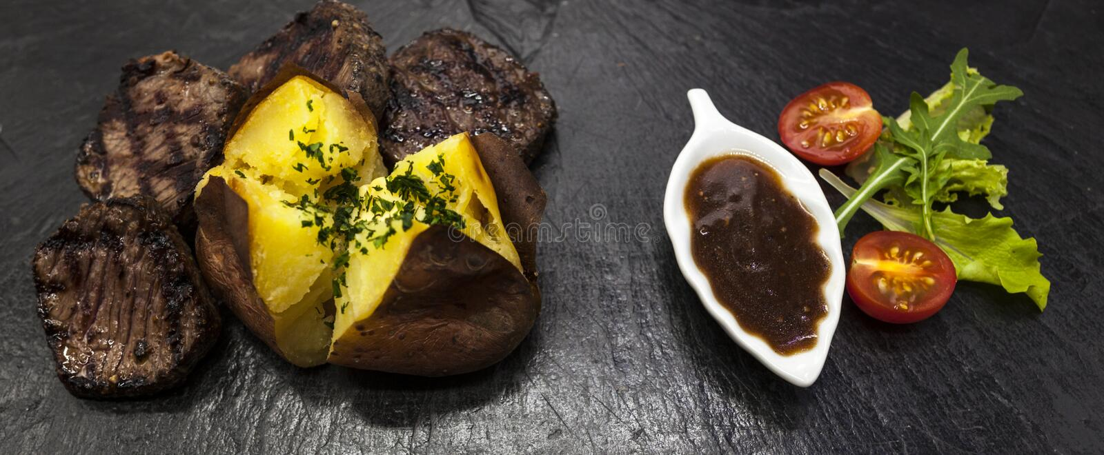 Delicious juicy hot roast beef cut into delicious pieces of meat and vegetables. Served on a black stone . Delicious juicy hot roast beef cut into delicious stock images