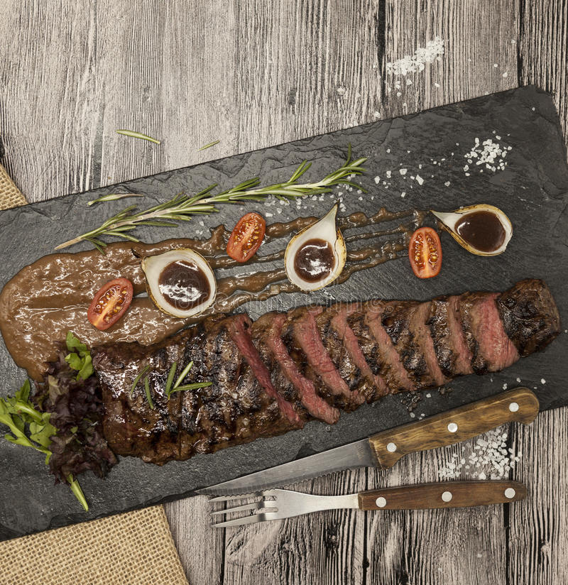 Delicious juicy hot roast beef cut into delicious pieces of meat and vegetables. Served on a black stone plate with a fork and kni. Fe and pepper stock photo