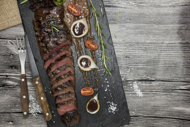 Delicious juicy hot roast beef cut into delicious pieces of meat and vegetables. Served on a black stone plate with a fork and kni. Fe and pepper stock image