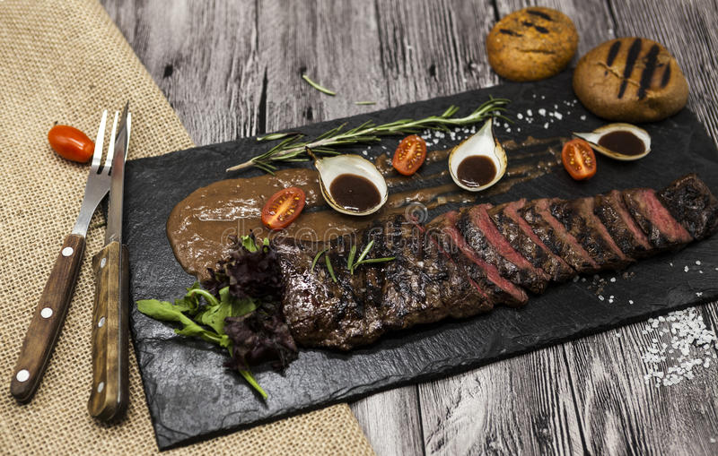 Delicious juicy hot roast beef cut into delicious pieces of meat and vegetables. Served on a black stone plate with a fork and kni. Fe and pepper stock photography