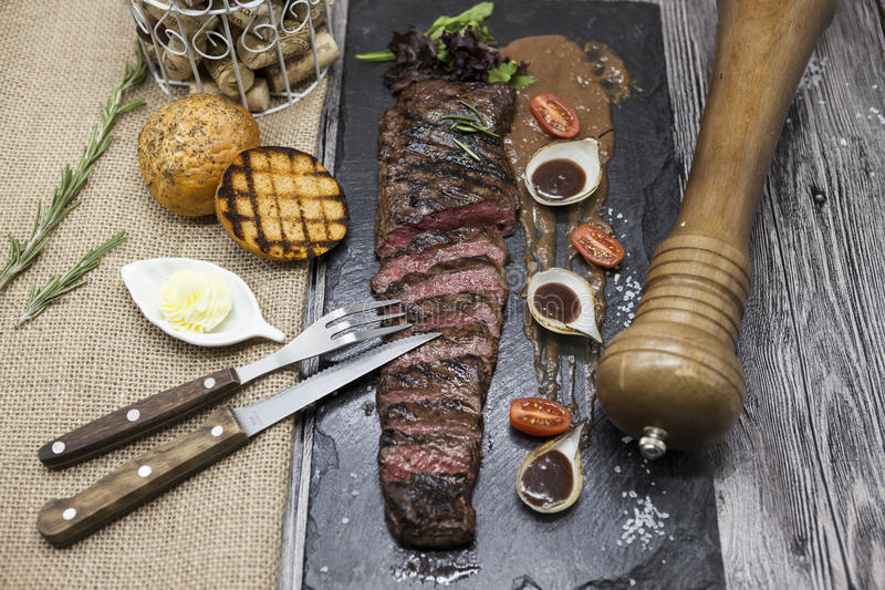 Delicious juicy hot roast beef cut into delicious pieces of meat and vegetables. Served on a black stone plate with a fork and kni. Fe and pepper royalty free stock photography