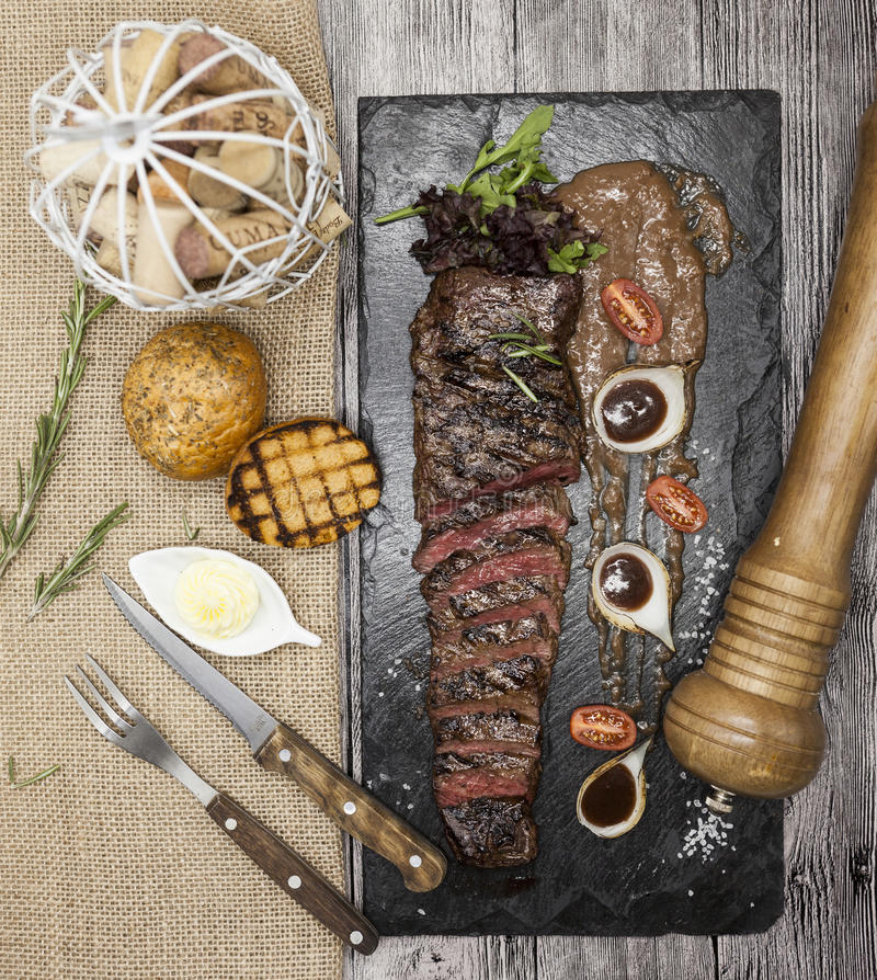 Delicious juicy hot roast beef cut into delicious pieces of meat and vegetables. Served on a black stone plate with a fork and kni. Fe and pepper stock images