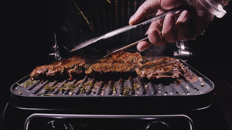 Delicious juicy meat steak cooking on grill. Aged prime rare roast grilling marble beef. Electric roaster, rosemary stock images
