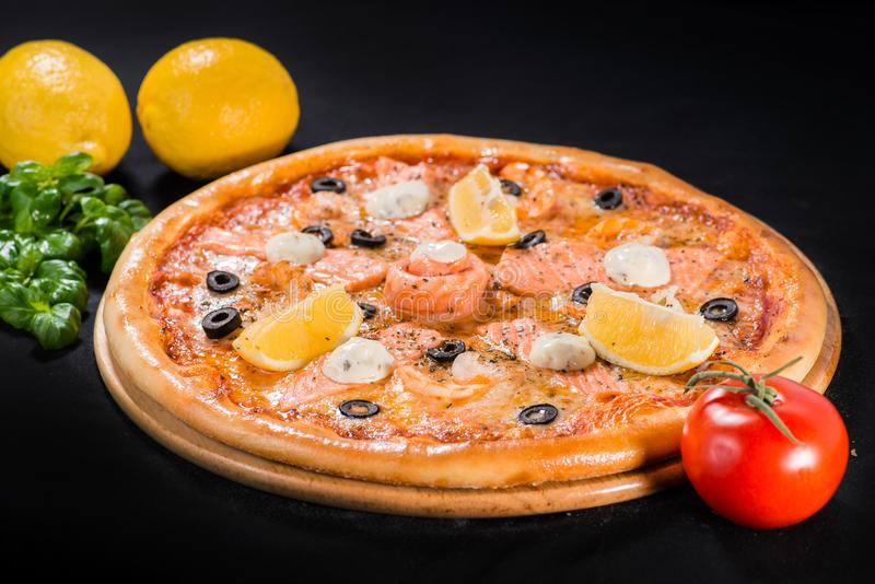 Delicious juicy pizza with salmon, lemon and olives on wooden bo stock image