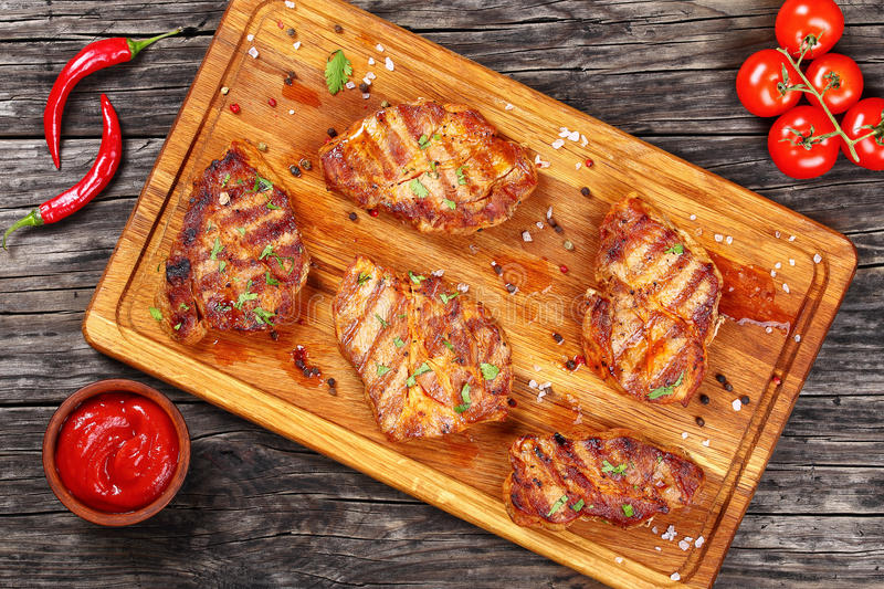 Delicious juicy pork chops, top view. Delicious juicy pork chops marinated in a honey, soy sauce and spices mixture, and grilled to a tender served on wooden royalty free stock photo