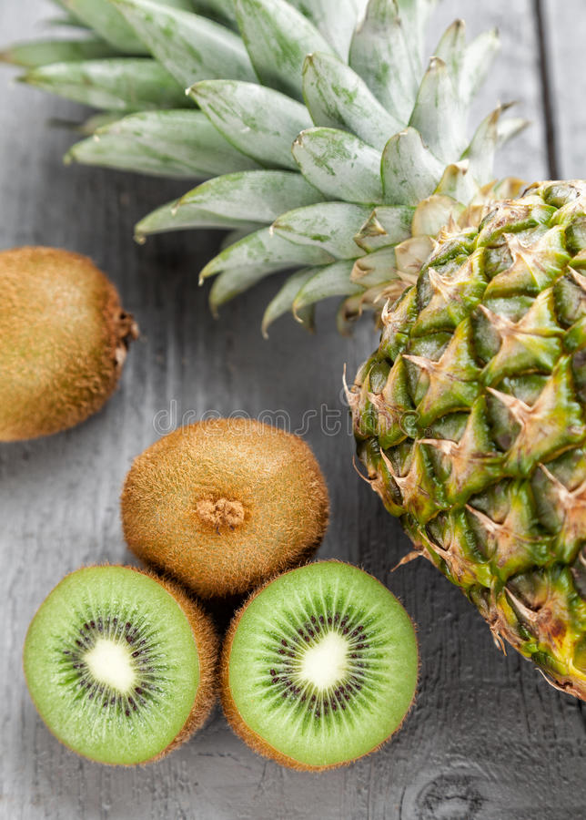 Delicious kiwi and pineapple fruit on grey wooden background royalty free stock photography