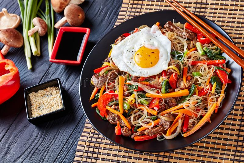 Delicious korean dish Japchae: on a black plate. Delicious korean dish Japchae: mix of glass noodles, beef and stir fried onion, bell pepper, garlic, spinach stock photography