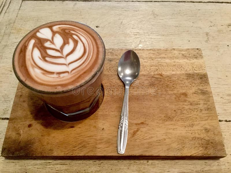 Delicious . latte design. Hot caffe mocha. top view. Drink. A caffè mocha, on a wooden table with spoon, also called mocaccino, is a chocolate-flavored stock photography