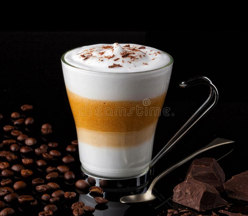 Latte macchiato with coffee beans an chocolate chunks stock images