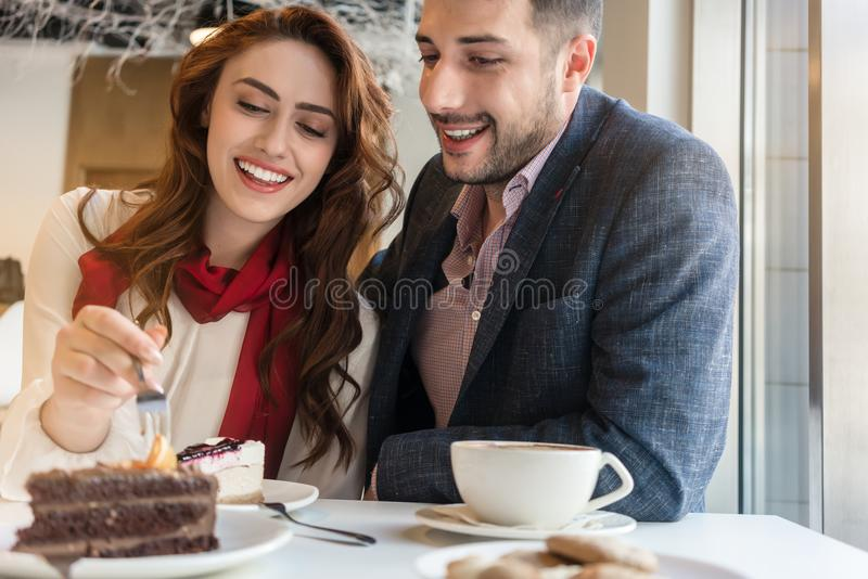 Delicious layered cake served with coffee on the table of a young couple. In love during romantic date in a trendy cafeteria royalty free stock photo