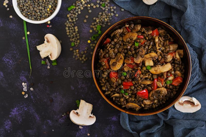 Delicious lentils with pepper and mushrooms on dark background.  royalty free stock photo