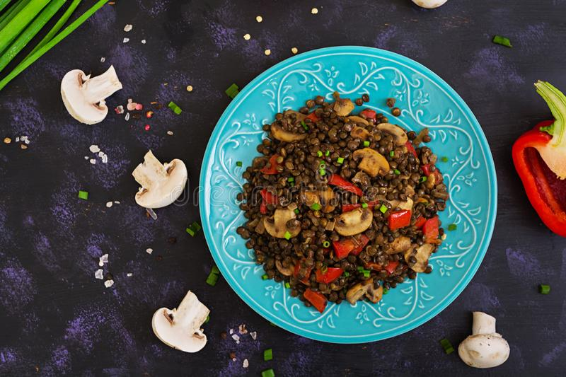 Delicious lentils with pepper and mushrooms on dark background.  royalty free stock photography