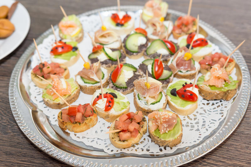 Delicious little sandwiches bites with bacon, cherry tomato, olives, cucumber, lettuce and corn on a tray royalty free stock photo