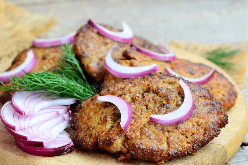 Fried cutlets made from chicken liver mince and vegetables. Fast simple liver cutlets on a wooden cutting board. Closeup royalty free stock photo