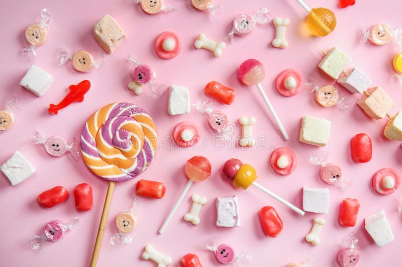 Delicious lollipops and sweets on color background stock photography