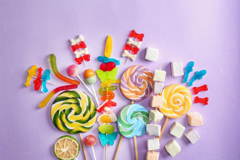 Delicious lollipops and sweets on color background royalty free stock photos