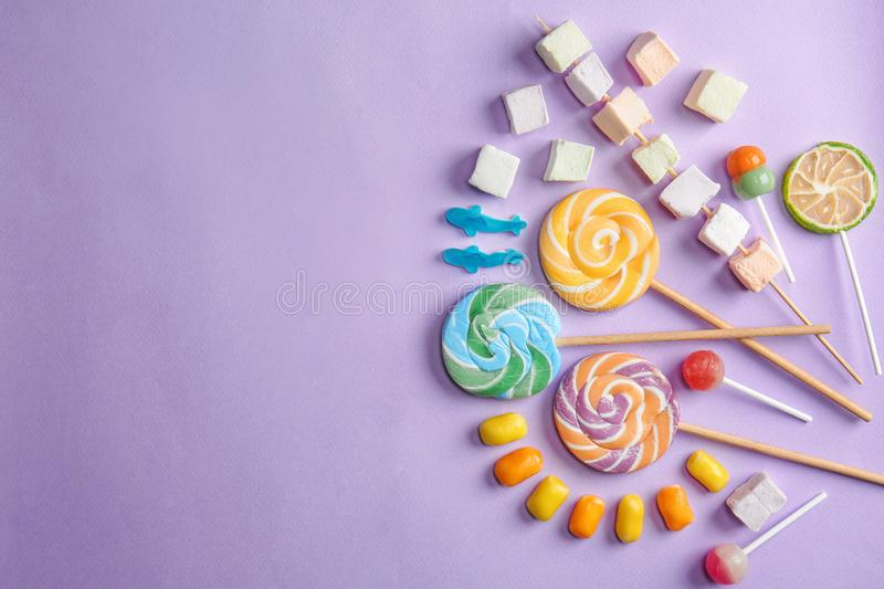 Delicious lollipops and sweets on color background stock photo