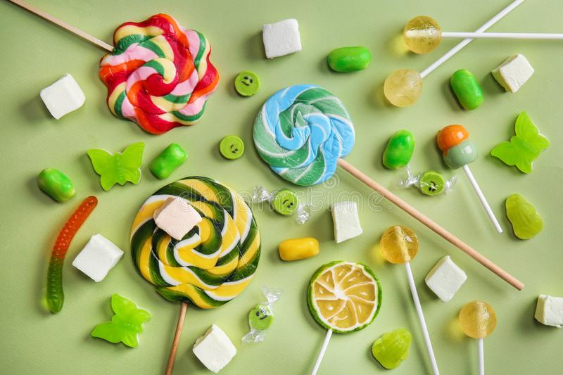 Delicious lollipops and sweets on color background stock photos