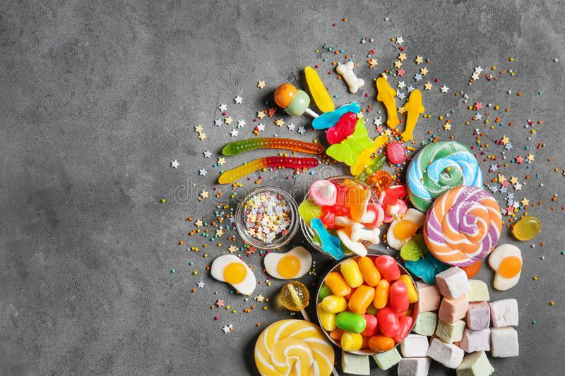 Delicious lollipops and sweets on grey background stock image