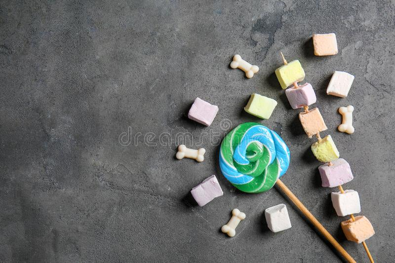 Delicious lollipops and sweets on grey background royalty free stock images