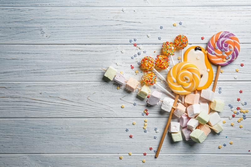 Delicious lollipops and sweets on white wooden background royalty free stock photos