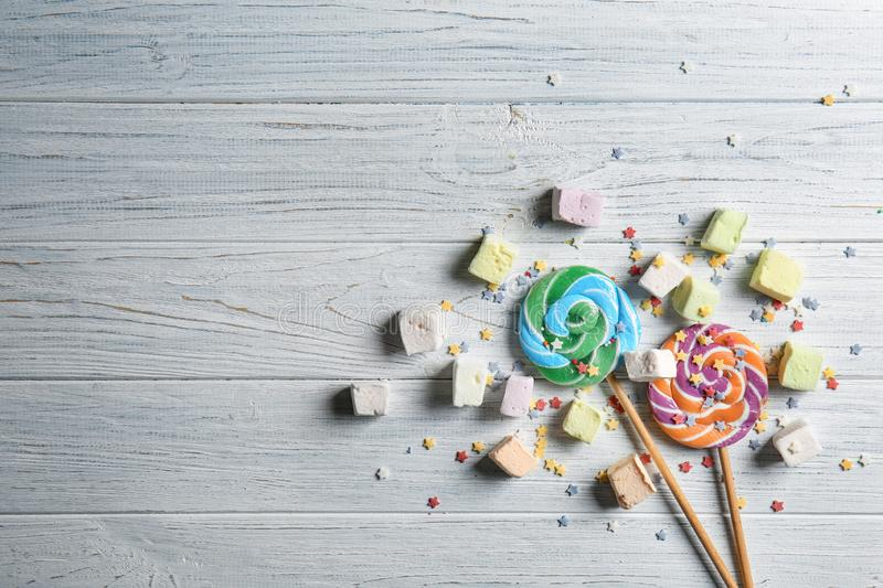 Delicious lollipops and sweets on white wooden background stock photography