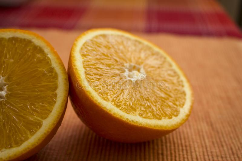 Delicious looking juicy halves of oranges on the table stock photo