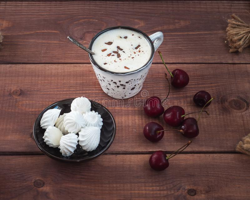 Delicious lunch with cherries, meringue cookies and coffee with cream in a ceramic mug. On a wooden tray stock photography