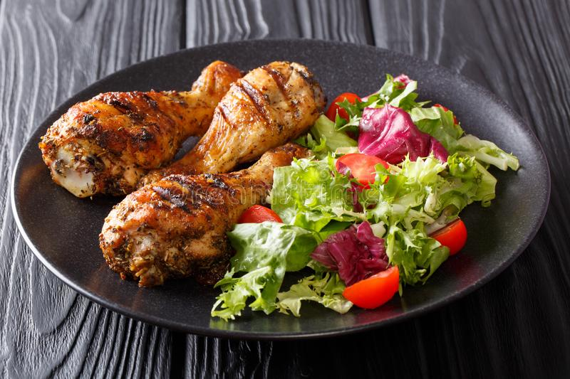 Delicious lunch: grilled chicken legs with fresh salad close-up. horizontal royalty free stock photos