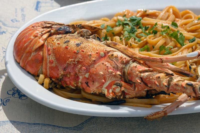 Delicious lunch by the sea. A white plate of spaghetti with huge lobsters on the grill. royalty free stock photography
