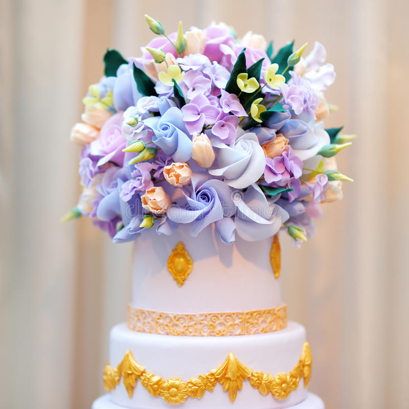 Delicious luxury white wedding or birthday cake. Decorated with cream colorful flowers stock image