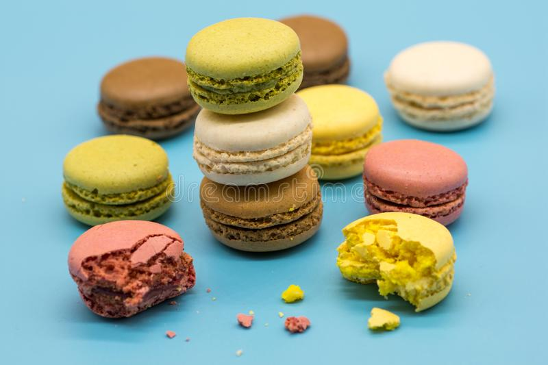 Delicious macarons full and bitten and crumbs arranged on colorful background royalty free stock photo
