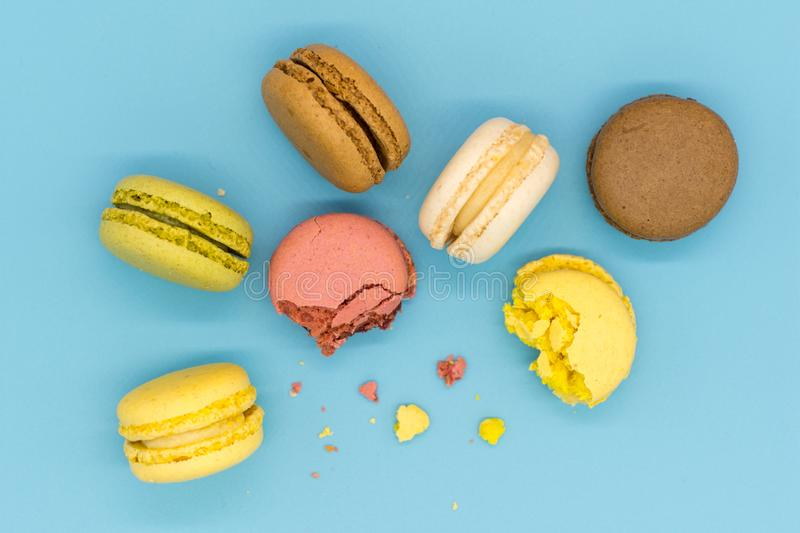 Delicious macarons full and bitten and crumbs arranged on colorful background top view stock photo