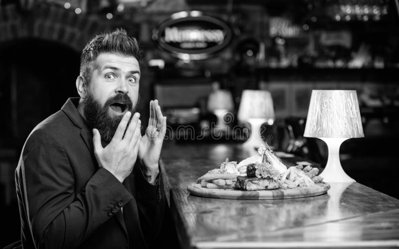 Delicious meal. Enjoy meal. Cheat meal concept. Hipster hungry eat pub fried food. Restaurant client. Hipster formal. Suit sit at bar counter. Man received meal royalty free stock photo