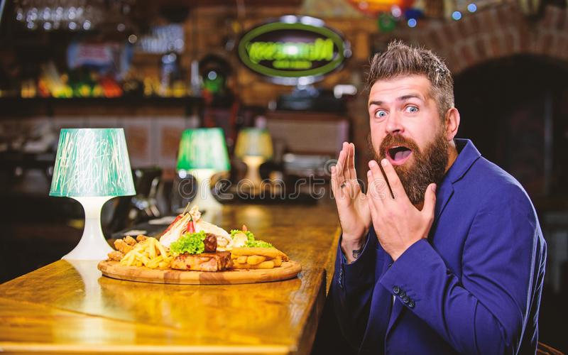 Delicious meal. Enjoy meal. Cheat meal concept. Hipster hungry eat pub fried food. Restaurant client. Hipster formal. Suit sit at bar counter. Man received meal royalty free stock image