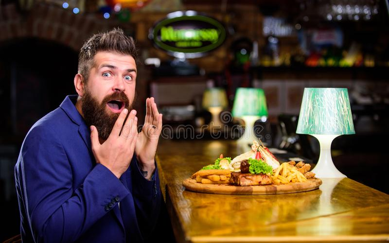 Delicious meal. Enjoy meal. Cheat meal concept. Hipster hungry eat pub fried food. Restaurant client. Hipster formal. Suit sit at bar counter. Man received meal royalty free stock photography