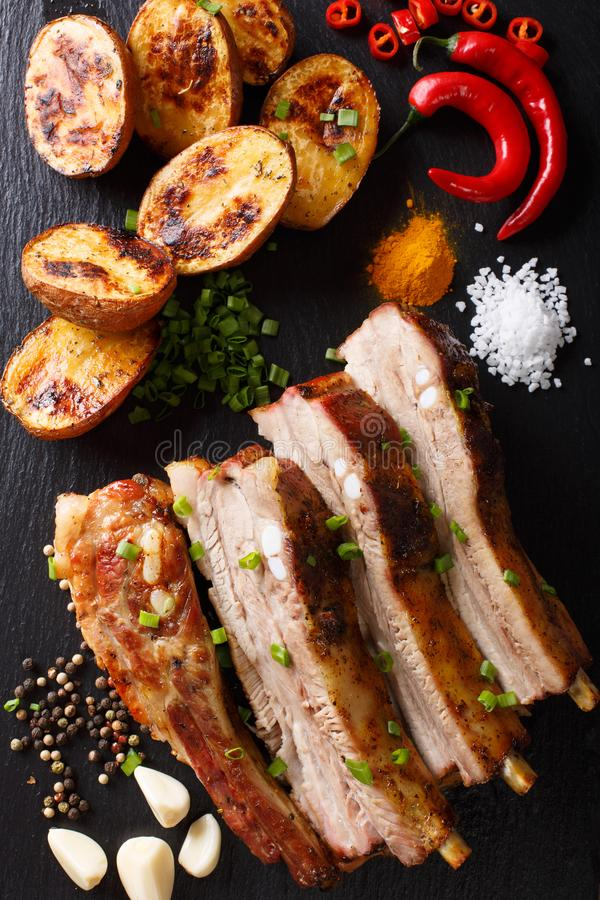 Delicious meal: fried ribs with baked potatoes and spices close-up on the table. vertical view from above stock image