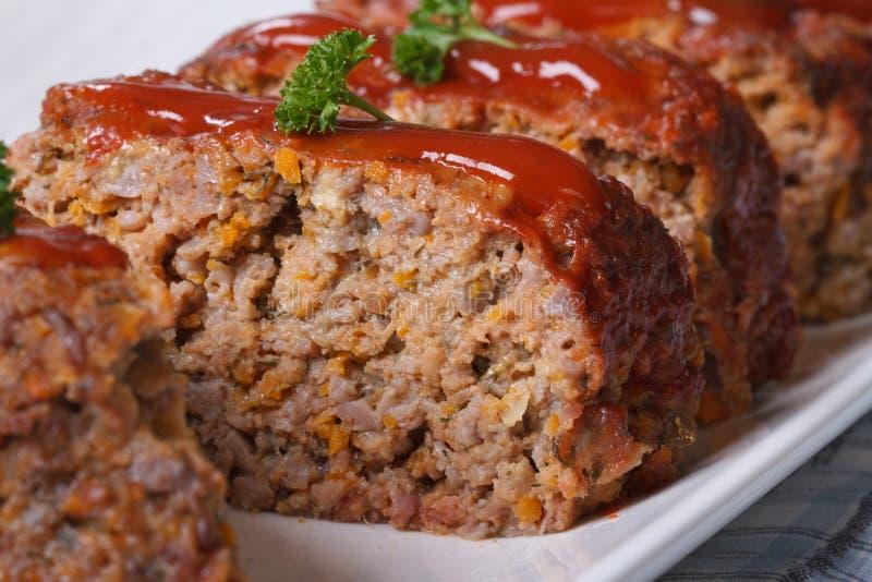 Delicious meat loaf with ketchup macro, horizontal. Delicious meat loaf with ketchup on a white plate, macro horizontal royalty free stock photos